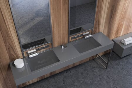 Top view of stylish bathroom with wooden walls, concrete floor and comfortable double sink with two mirrors standing on gray countertop. 3d rendering