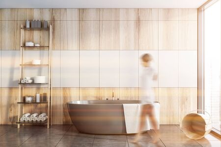 Blurry young woman walking in stylish sunlit bathroom with white and wooden walls, tiled floor, comfortable grey bathtub and shelves with cosmetic products. Concept of spa. Tone image