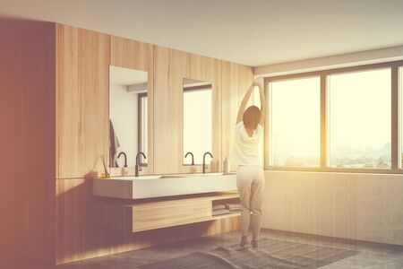 Rear view of young woman in pajamas standing in sunlit bathroom with with white and wooden walls, concrete floor, comfortable double sink and window with nice view. Toned image double exposure Zdjęcie Seryjne