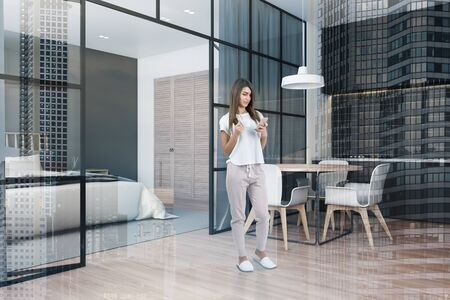 Young woman with coffee standing in stylish kitchen with gray countertops, round dining table and bedroom with king size bed and built in wardrobe in background. Toned image double exposure Stock Photo