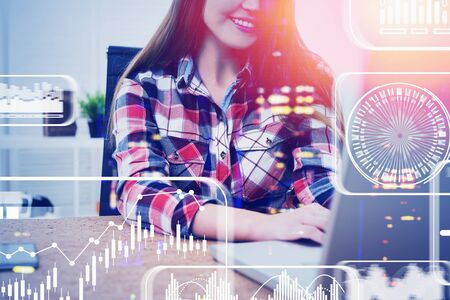 Unrecognizable smiling woman in casual clothes working on laptop in office with double exposure of blurry futuristic infographic interface. Concept of software development. Toned image