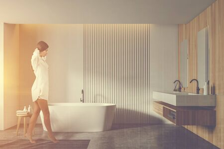 Pretty young woman walking in stylish bathroom with white and wooden walls, concrete floor, comfortable bathtub and double sink with two vertical mirrors. Toned image double exposure