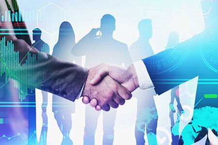 Two businessmen shaking hands with business people silhouettes in background and double exposure of infographics interface. Toned blurry image
