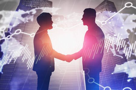 Silhouettes of business people shaking hands in city with double exposure of blurry world map and graphs. Concept of international business. Toned image