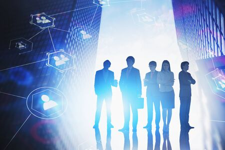 Silhouettes of diverse business people in city with double exposure of social network interface. Concept of job search. Toned blurry image