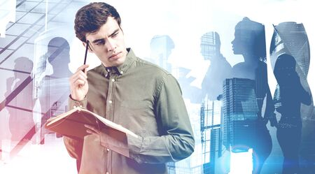Pensive young man with notebook standing in abstract city with diverse business people silhouettes in background. Concept of teamwork. Toned blurry image double exposure 版權商用圖片