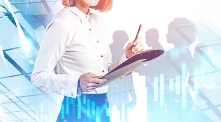 Unrecognizable businesswoman with clipboard and members of her team working together in city with double exposure of blurry graphs. Toned image