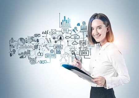 Smiling young businesswoman with clipboard standing near gray wall with creative business plan sketch drawn on it. Stock Photo