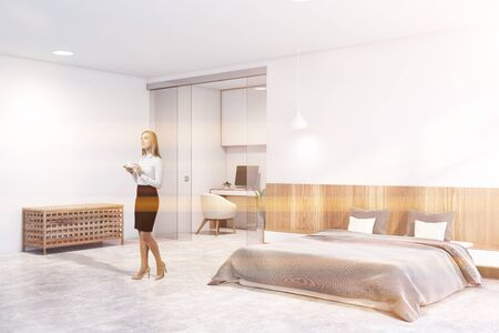 Blonde woman standing in Scandinavian master bedroom with white and wooden walls, concrete floor, comfortable king size bed and home office in background. Toned image
