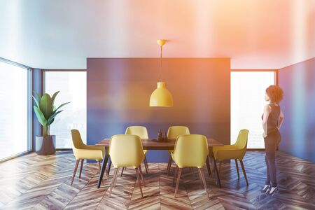 Beautiful African American woman standing in modern dining room with blue walls, wooden floor, panoramic window and wooden table with yellow chairs. Toned image