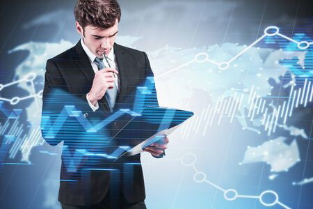 Pensive young businessman standing with clipboard over blurry background with world map and forex graphs. Concept of fintech and market analysis. Toned image double exposure