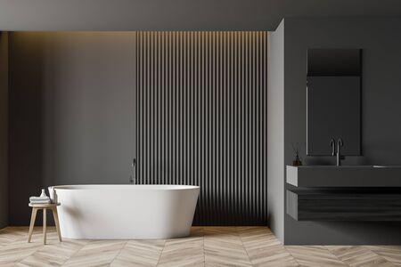Interno di un ampio bagno con pareti grigie, pavimento in legno, comoda vasca da bagno e lavandino in piedi su un piano di lavoro in legno scuro. rendering 3d