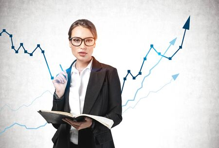 Serious young businesswoman with glasses and notebook standing near concrete wall with graphs drawn on it. Concept of business education and financial growth