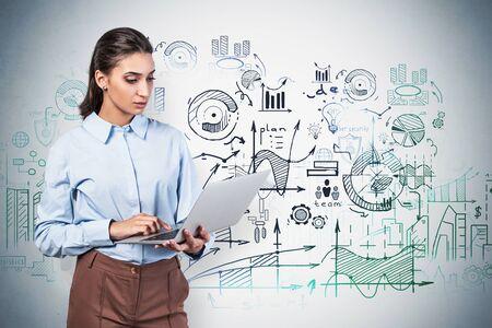 Grave empresaria joven con cabello oscuro trabajando con laptop cerca de muro de hormigón con boceto de plan de negocios dibujado en él Concepto de estrategia empresarial y educación. Imagen borrosa Foto de archivo