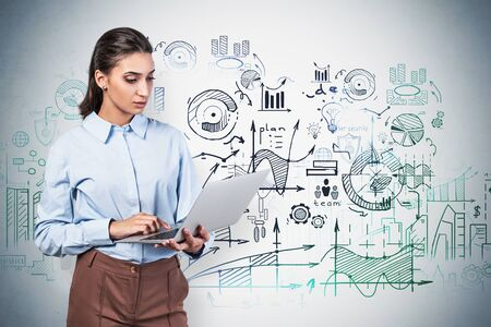 Serious young businesswoman with dark hair working with laptop near concrete wall with business plan sketch drawn on it. Concept of business strategy and education. Blurry image Фото со стока