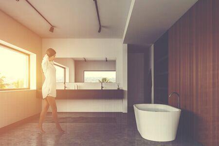 Piękna młoda kobieta spaceru w stylowej nasłonecznionej łazience z białymi i drewnianymi ścianami, wygodną wanną i szarą umywalką. Stonowany obraz podwójna ekspozycja Zdjęcie Seryjne