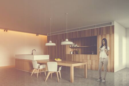 Young woman with coffee standing in modern kitchen corner with white walls, wooden countertops and island with built in sink and white chairs. Toned image double exposure Stock Photo