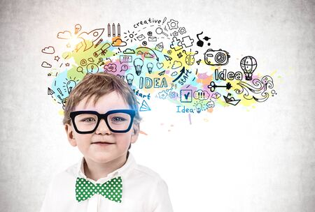 Adorable little boy in glasses and green bowtie standing near concrete wall with colorful creativity sketch drawn on it. Concept of development and education