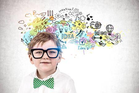 Entzückender kleiner Junge in Gläsern und grüner Fliege, der in der Nähe der Betonmauer steht, mit bunter Kreativitätsskizze darauf gezeichnet. Konzept der Entwicklung und Bildung
