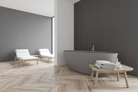 Corner of spacious spa bathroom with gray and white walls, wooden floor, comfortable bathtub and two massage benches near the window. Concept of relaxation and luxury resort. 3d rendering Reklamní fotografie