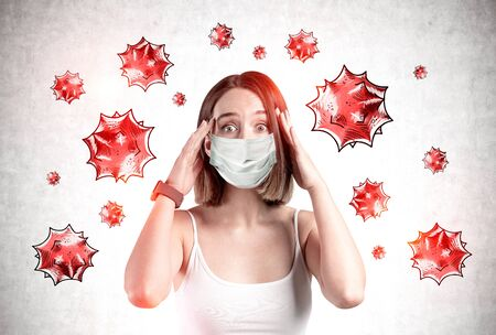 Scared young girl in medical mask standing near concrete wall with virus molecules drawn on it. Concept of coronavirus and flu panic. Toned image