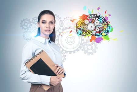 Serious young woman with dark hair and notebooks standing near concrete wall with colorful brain with gears drawn on it. Concept of brainstorming and education. Banque d'images