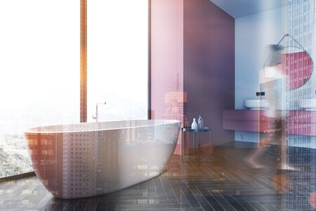Blurry young woman walking in modern bathroom with white and pink walls, black wooden floor, bathtub near the window and round double sink. Toned image double exposure