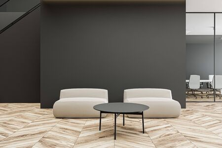 Comfortable white armchairs standing near round coffee table in modern office waiting room with dark grey walls, wooden floor, staircase and conference room in background. 3d rendering Stok Fotoğraf