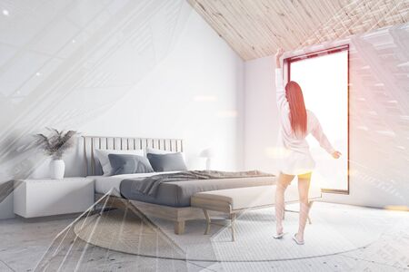 Young woman in pajamas standing in attic bedroom corner with white walls, stone floor, king size bed and bench standing on round carpet. Toned image double exposure Archivio Fotografico
