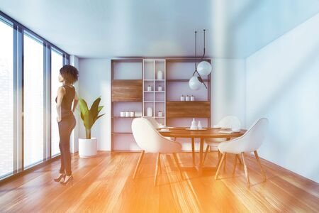 Beautiful African American woman standing in modern panoramic dining room with white walls, wooden floor, round table with white chairs and cupboard. Window with blurry cityscape. Toned image