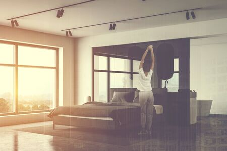 Rear view of woman standing in sunlit bedroom corner with white and glass walls, comfortable king size bed and bathroom in background. Toned image double exposure