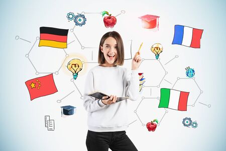 Smiling teen girl with notebook standing near grey wall with colorful international education sketch drawn on it. Concept of foreign languages and career choice. Stock Photo