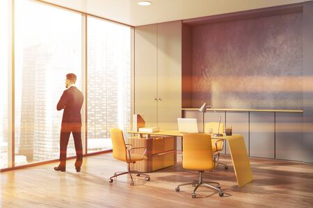 Young manager standing in panoramic CEO office with gray walls, wooden floor and stylish table with yellow chairs. Concept of leadership. Toned image