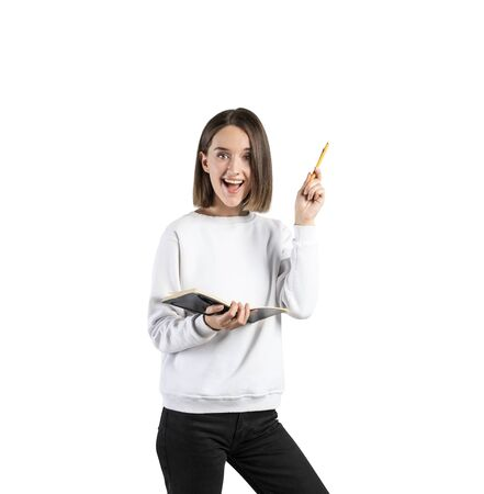 Isolated portrait of happy teen girl in casual clothes holding notebook and pen. Concept of bright idea and education
