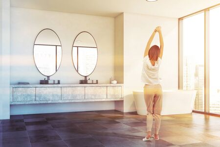 Rear view of young girl in pajamas standing in panoramic bathroom with white walls, tiled floor, round sink with oval mirrors and comfortable bathtub. Toned image