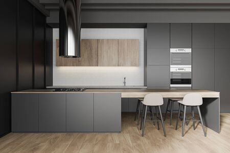 Interior of stylish kitchen with black and white walls, wooden floor, grey countertops and long bar with stools and built in cooker. 3d rendering