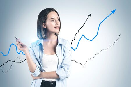 Pensive young businesswoman in smart casual clothes standing near grey wall with growing graphs drawn on it. Concept of stock market and business education.