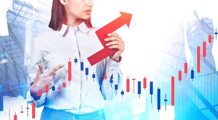 Unrecognizable young businesswoman pointing at red growing business chart standing over cityscape background. Double exposure of forex graph. Concept of financial growth and stock market. Toned image Фото со стока