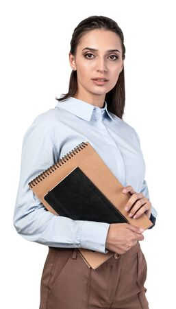 Isolated portrait of serious young college student or businesswoman with long dark hair holding notebooks. Concept of education and planning