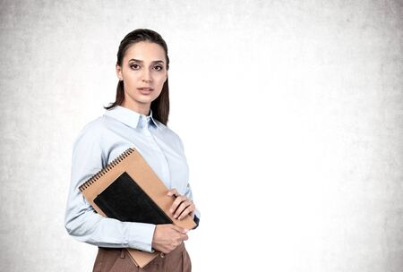Portrait of serious young college student or businesswoman with long dark hair holding notebooks. Concrete wall background. Concept of education and planning. Mock up