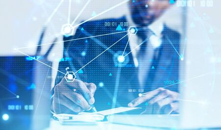 Unrecognizable African American businessman writing in blurry office with double exposure of creative network interface. Concept of internet connection and communication. Toned image Banco de Imagens