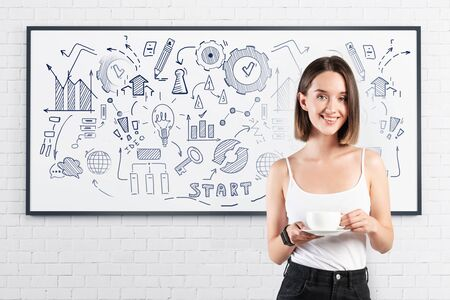 Cheerful young woman in casual clothes drinking coffee near whiteboard with creative business plan sketch drawn on it. Concept of business education and strategy Stock Photo