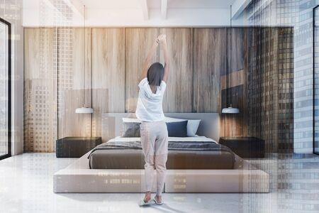 Rear view of woman in pajamas standing in modern bedroom with white and wooden walls, concrete floor and comfortable king size bed. Toned image double exposure Stock fotó