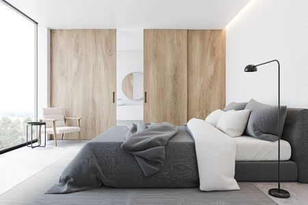 Interior of minimalistic bedroom with white walls, concrete floor, comfortable king size bed with grey blanket and bathroom with sink and round mirror in background. Wooden sliding door. 3d rendering