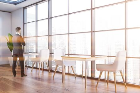 Rear view of young businessman standing in panoramic restaurant with white walls, wooden floor, square tables with wjote chairs and window with blurry cityscape. Toned image