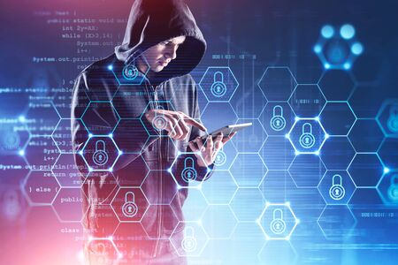 Young hacker in hoodie with tablet committing cyber crime over blurry blue background with double exposure of cyber security interface. Toned image