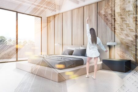 Rear view of woman in nightgown standing in modern bedroom with white and wooden walls, concrete floor and comfortable king size bed. Balcony with nice view. Toned image double exposure