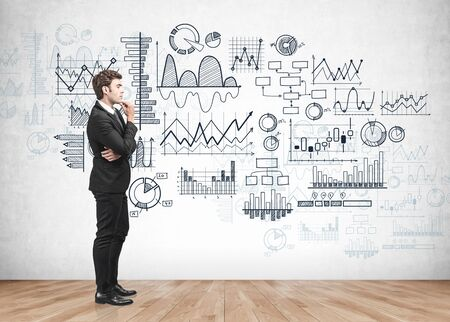 Side view of young European businessman thinking about investment standing near concrete wall with financial graphs drawn on it. Concept of market analysis