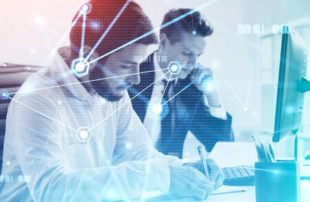 Two young businessmen working together in blurry office with double exposure of creative futuristic network interface. Concept of internet connection and technology. Toned image