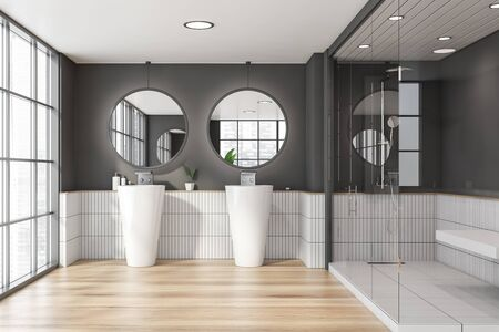 Interior of panoramic hotel bathroom with grey and white tiled walls, wooden floor, original double sink with two round mirrors and shower stall with glass walls. 3d rendering